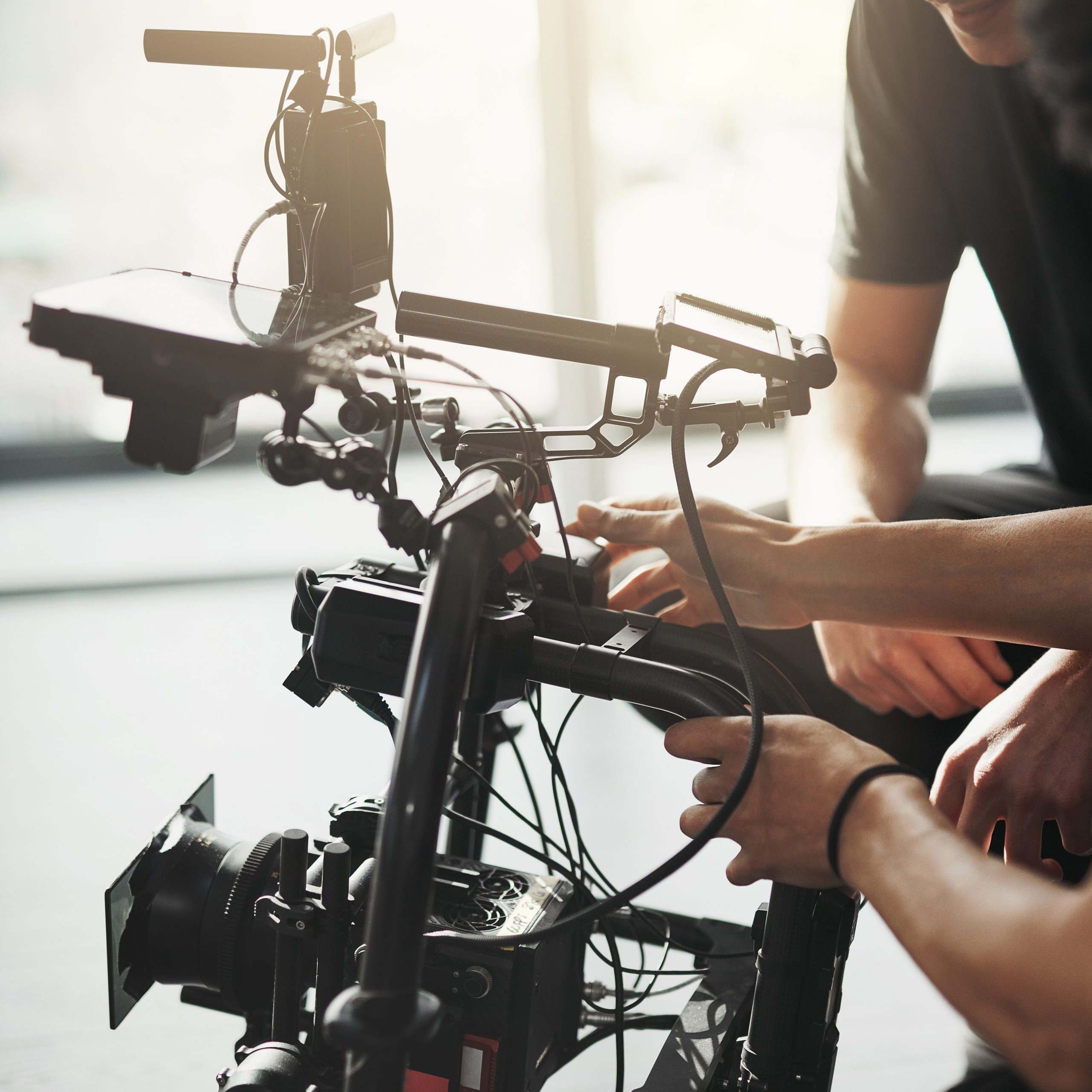 Behind the scenes shot of two young camera operators shooting a scene with a state of the art camera inside of a studio during the day